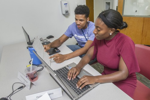 Mustafa Shabazz of the University of Pennsylvania (left) and Hyidea Burgess of Alabama A&M University develop software that can quickly balance complex oxidation-reduction chemical reactions.
