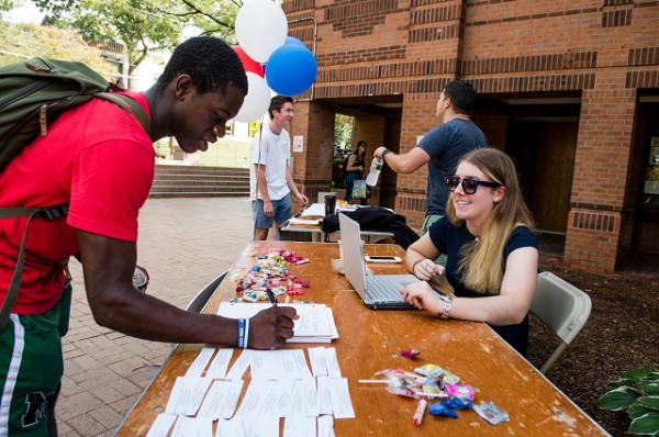 College students register to vote at a campus civics fair. According to CIRCLE polling, interest among young voters in the 2018 midterm elections is at historic levels
