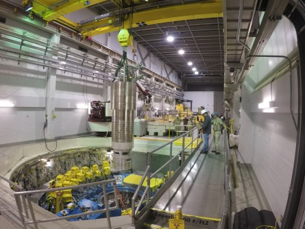 A heavy overhead crane is used to lower the 64,000-pound inner reflector plug into position, right in the heart of the Spallation Neutron Source.